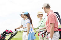 Popular : Friends talking while walking at golf course against clear sky