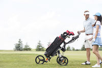 Popular : Friends with equipment talking while walking at golf course against clear sky