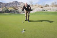 Popular : Full length of senior male golfer celebrating a putt at golf course