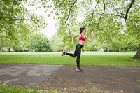 Full length side view of fit woman jogging in park