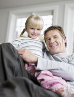 Girl  3-4  sitting in father s lap in house portrait low angle view