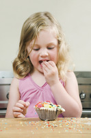 Girl eating candies from cupcake