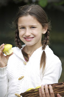 Girl holding a basket of apples while eating an apple