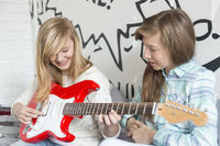 Girl listening to sister playing electric guitar at home