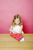 Girl wrapping up a present
