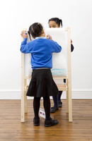 Girls drawing on drawing board