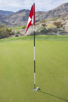 Golf ball and flag at course