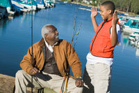 Grandfather and grandson fishing boy gesturing