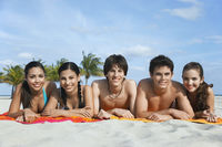 Group of teenagers  16-17  lying in row on beach towels portrait