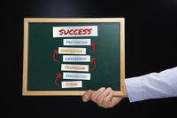 Hand holding blackboard with success concept