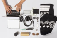 Hands using a laptop with men clothing and accessories