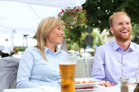 Happy businessman and businesswoman sitting at outdoor restaurant