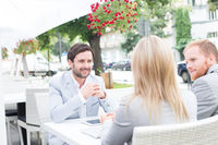 Popular : Happy businessman discussing with colleagues at sidewalk cafe