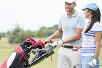 Popular : Happy friends with bag talking at golf course