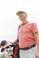 Popular : Happy middle-aged man looking away while carrying golf bag against clear sky