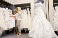 Happy mother and daughter shopping together for wedding gown in boutique