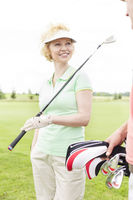 Popular : Happy woman looking at male friend at golf course
