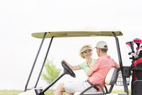 Popular : Happy woman looking at man while sitting in golf cart
