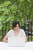 Happy young businesswoman using laptop at desk