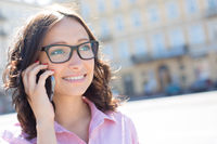 Happy young woman looking away while using smart phone on sunny day