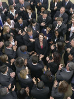 Large group of business people clapping surrounding woman looking up elevated view