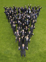 Large group of business people standing in triangle formation cheering elevated view