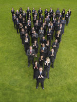 Large group of business people standing in triangle formation clapping elevated view