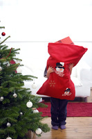 Little boy hugging a bag full of gifts