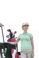 Popular : Low angle view of smiling golfer standing against clear sky