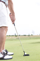 Popular : Low section of mid-adult man playing golf against clear sky