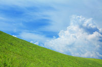 Lush  green hill with blue sky and clouds