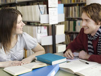 Male and female student talking in library