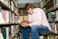 Male college student sitting reading in library