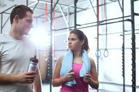 Popular : Man and woman looking at each other in crossfit gym