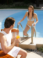 Man enjoying drink by the pool side with his girlfriend climbing out from the pool