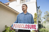 Man holding sign outside house