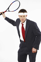 Man in business suit playing tennis