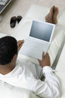 Man reclining on sofa using laptop high angle view