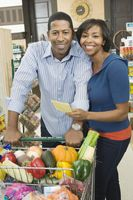 Mature couple stand with grocery shopping in supermarket aisle