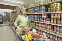 Mature woman with grocery shopping in supermarket aisle