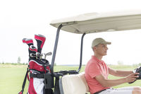 Popular : Middle-aged man driving golf cart at course