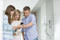 Middle-aged man with daughters using smart phone at home