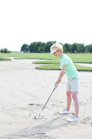 Popular : Middle-aged woman playing golf at course against clear sky