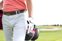 Popular : Midsection of man carrying golf club bag while walking at course