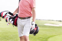 Popular : Midsection of man with golf club bag standing at course