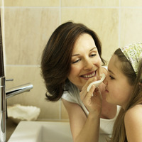 Mother cleaning her daughter s face with a facial cotton