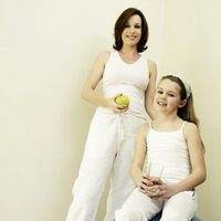 Mother holding a green apple while daughter holding a glass of water