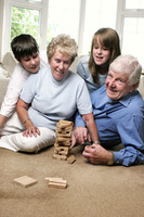 Old couple playing building blocks whiles their grandchildren watching