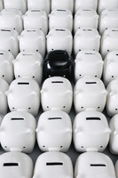 One black piggy bank surrounded by white piggy banks