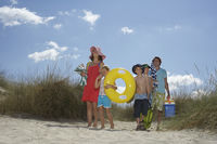 Parents with three children  6-12  carrying beach accessories